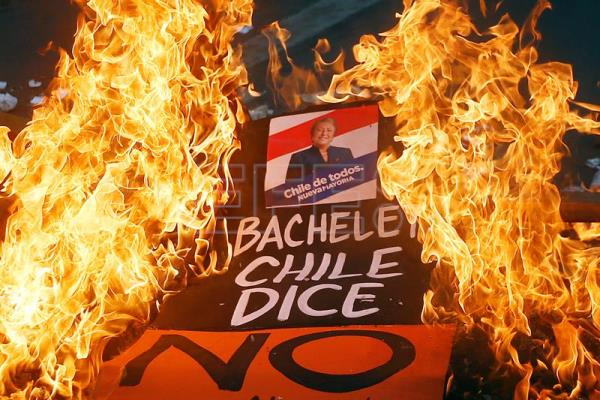 A poster bearing the image of Chilean President Michelle Bachelet is burned during a march by some 80,000 students demanding an overhaul of the educational system. EFE