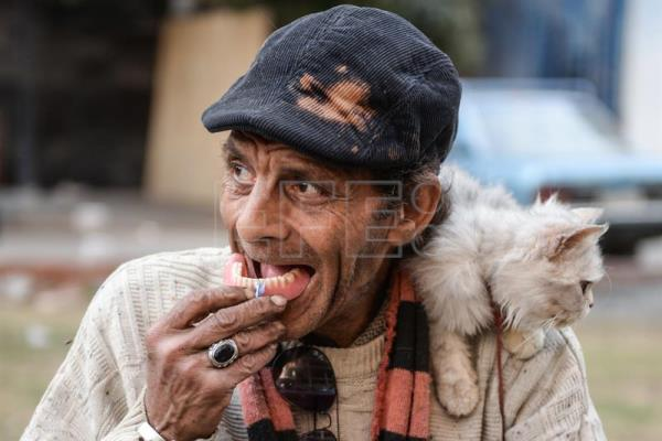 Elderly Egyptian man, Naguib, adjusts his removable dentures as he sits outside his home where he lives along with stray dogs and cats at in Cairo, Egypt, Mar. 10, 2017. EPA/MOHAMED HOSSAM