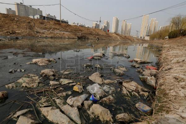 (FILE) Plastic waste pollutes a river in Beijing, China, 19 March 2016. EPA/WU HONG