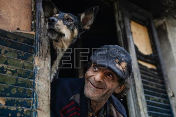 Elderly Egyptian man, Naguib, and a stray dog look out from the window of his burnt-out room where he lives along with stray dogs and cats at in Cairo, Egypt, Mar. 11, 2017. EPA/MOHAMED HOSSAM