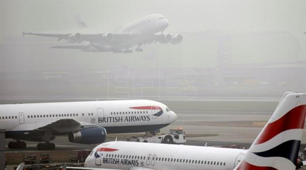 Planes of the British Airways airline gather on the runway as a plane of Malaysia Airlines takes off during thick fog delays departures from Terminal 5 Heathrow Airport in London, Britain, on Jan. 23, 2017. EPA/WILL OLIVER