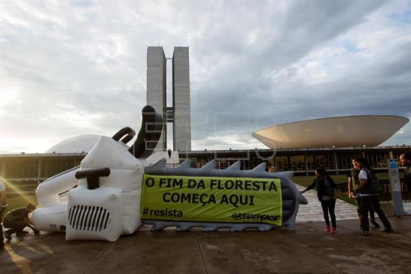 "A group of Greenpeace activists gather in front of the Brazilian Congress, where they displayed a plastic chainsaw 8 meters (26 feet) long, together with a poster that read: ""The end of the forests starts here,"" in Brasilia, Brazil on May 16, 2017. EFE/Joedson Alves"