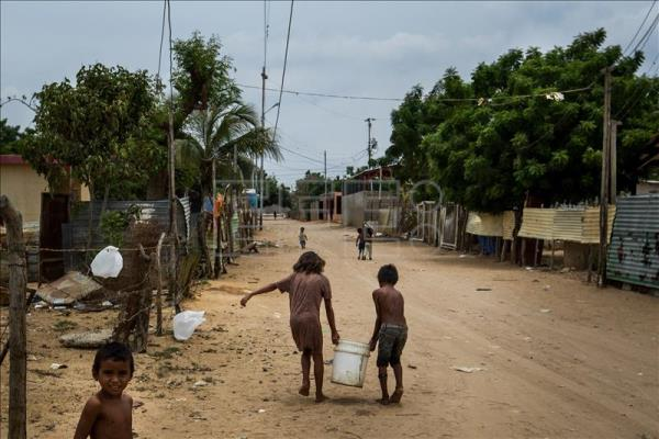 Two boys carry a container filled with water in the Venezuelan town of Canchancha. EFE/File