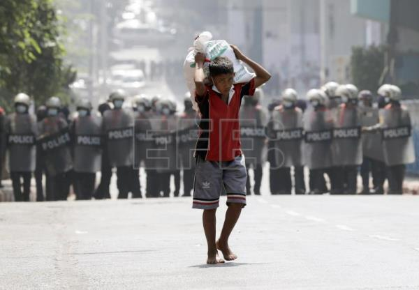 Myanmar police charge at night protest in Yangon neighborhood