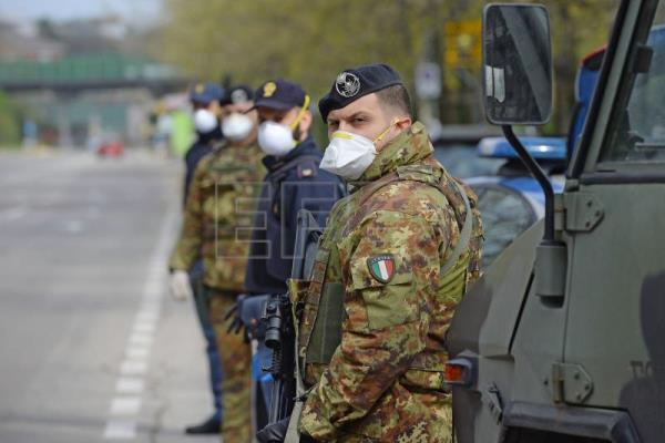 Italian soldiers and law enforcement officers conduct checks on drivers during coronavirus containment measures