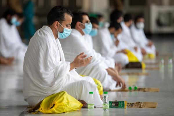 Muslims perform Hajj pilgrimage wearing masks with disinfectant in hand