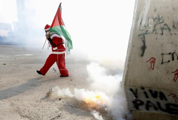 A Palestinian protester dressed as Santa Clause covers his face as he stands amid tear gas fired by Israeli soldiers during a demonstration in the West Bank city of Bethlehem, Dec. 23, 2017. EPA-EFE/ABED AL HASHLAMOUN