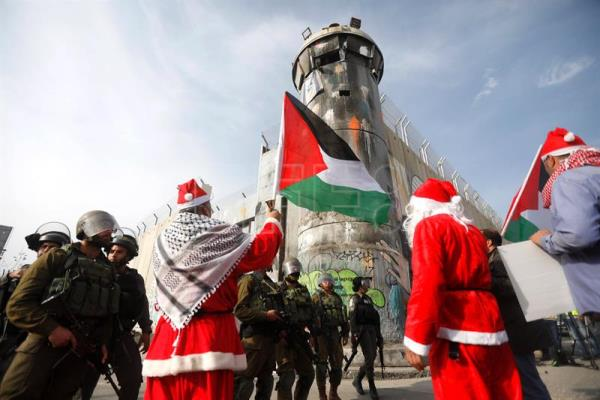 Palestinian protesters dressed as Santa Claus stand in front of Israeli soldiers during a demonstration in the West Bank city of Bethlehem, Dec. 23, 2017. EPA-EFE/ABED AL HASHLAMOUN
