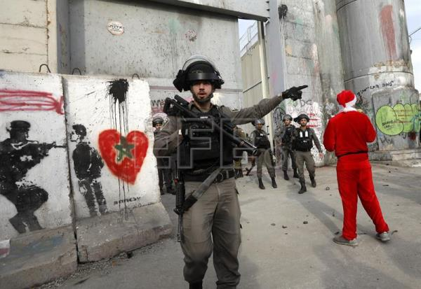 A Palestinian protester dressed as Santa Clause stands near Israeli soldiers during a demonstration in the West Bank city of Bethlehem, Dec. 23, 2017. EPA-EFE/ABED AL HASHLAMOUN