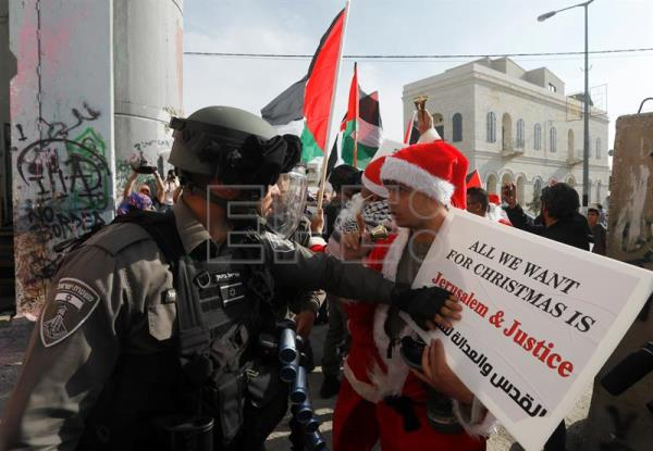 Israeli soldier argues with a Palestinian protester dressed as Santa Claus during a demonstration in the West Bank city of Bethlehem, Dec. 23, 2017. EPA-EFE/ABED AL HASHLAMOUN