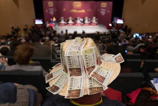 A man wearing a hat covered with lottery tickets attend the 'El Nino' (The Child) lottery draw in Avila, central Spain, 06 January 2018. EPA-EFE/RAUL SANCHIDRIAN