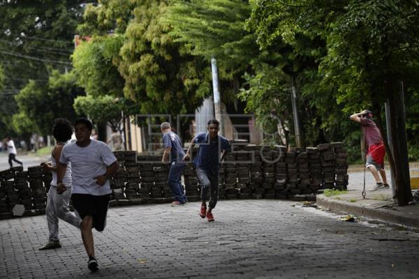 Demonstrators run during clashes with authorities in the neighborhoods of Managua, Nicaragua, June 11, 2018. EPA-EFE/Bienvenido Velasco