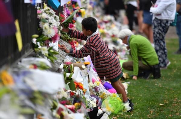 A child places flowers at a makeshift memorial for the victims of the mosque mass murders at the Botanical Gardens in Christchurch, New Zealand, Mar. 16, 2019. EPA-EFE/MICK TSIKAS AUSTRALIA AND NEW ZEALAND OUT