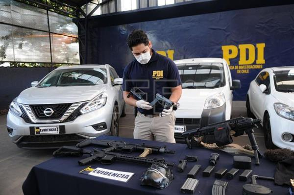 Photograph provided by Chile's Investigative Police (PDI) of an officer displaying the firearms and ammo seized from a cocaine ring operating in south Santiago, Chile, Feb. 13, 2018. EPA-EFE/PDI