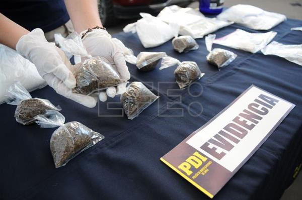 Photograph provided by Chile's Investigative Police (PDI) of an officer holding part of the drugs seized from a cocaine ring operating in south Santiago, Chile, Feb. 13, 2018. EPA-EFE/PDI