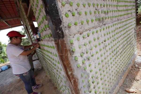 Photograph provided Oct 7 showing a volunteer assembling the wall of a community center built using plastic bottles in Las Veraneras, Panama, Oct 5, 2018. EPA-EFE/Bienvenido Velasco