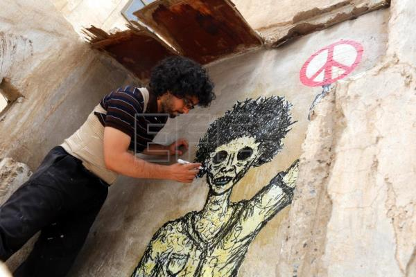 Yemeni artist Murad Subay works on a graffiti on a wall protesting the country's three-year conflict, at a street in Sana'Äôa, Yemen, May 14, 2018. EPA-EFE/YAHYA ARHAB