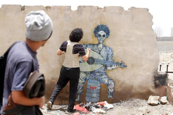 Yemeni artist Murad Subayi works on a graffiti on a wall protesting the country's three-year conflict, at a street in Sana'a, Yemen, May 14, 2018. EPA-EFE/YAHYA ARHAB