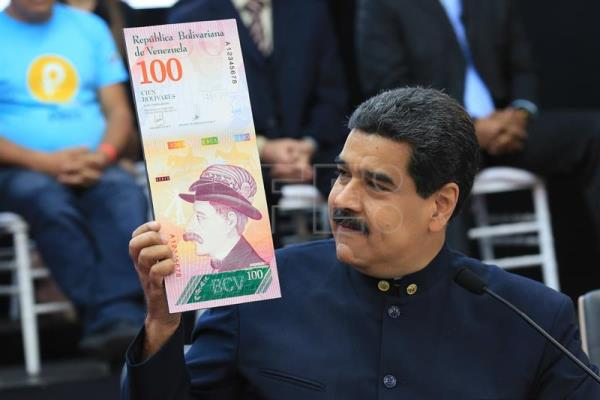 A handout photo made available by Miraflores Palace shows Venezuelan President Nicolas Maduro holding an enlarged image of the new 100 Venezuelan Bolivar note during a press conference in Caracas, Venezuela, 22 March 2018.  EPA-EFE/MIRAFLORES PRESS HANDOUT EDITORIAL USE ONLY/NO SALES