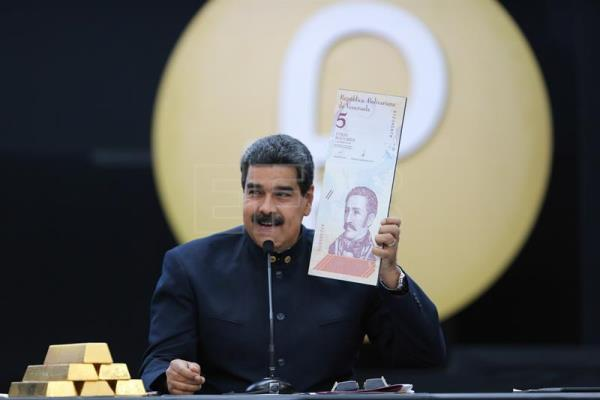 A handout photo made available by Miraflores Palace shows Venezuelan President Nicolas Maduro holding an enlarged image of the new five Venezuelan Bolivar note during a press conference in Caracas, Venezuela, 22 March 2018.  EPA-EFE/MIRAFLORES PRESS HANDOUT EDITORIAL USE ONLY/NO SALES
