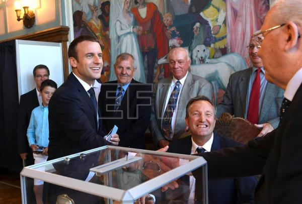 French President Emmanuel Macron (L) shakes hands with a voting official after voting in the second round of the French legislative elections at the City Hall in Le Touquet, France, 18 June. EFE