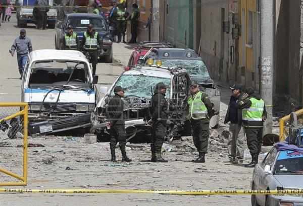 Police stand guard over damaged cars in the aftermath of an explosion in Oruro, Bolivia, Feb. 14, 2018. EPA-EFE/MARTIN ALIPAZ
