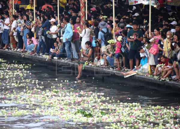 Devotees shower golden Buddha barge with lotus flowers at Thai festival
