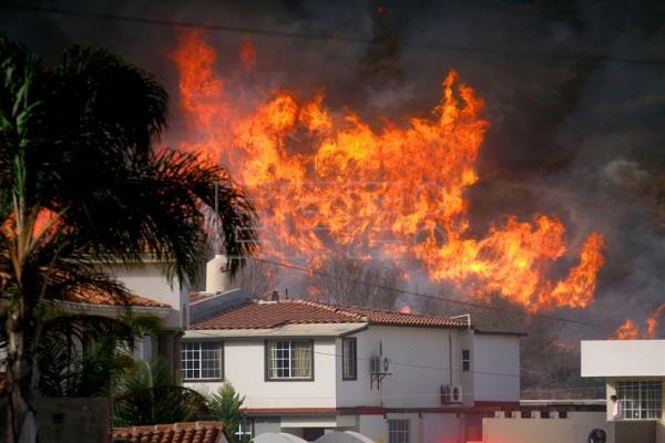 A fire rages in a residential area in Ensenada, in the state of Baja California Sur, Mexico, Dec. 7, 2017. EPA-EFE/Alejandro Zepeda
