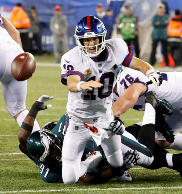 New York Giants quarterback Eli Manning (C) is tackled down by Philadelphia  Eagles defensive e0f2b9da6