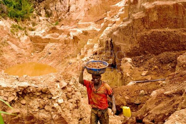 A Congolese mine worker carries gold rich earth out of pit for water processing in Chudja, Ituri province in the east of the Democratric Republic of the Congo, on June 18, 2009. EPA-EFE FILE/MARC HOFER