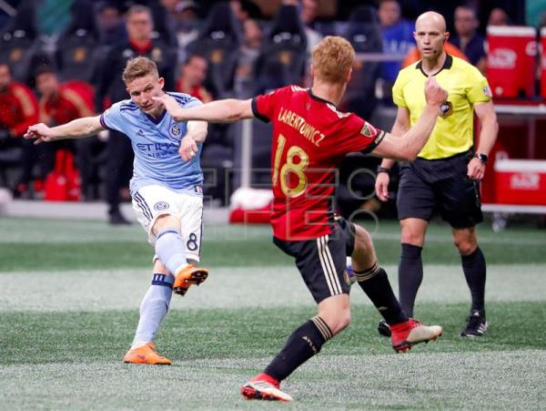 New York City midfielder Alexander Ring (L) of Finland shoots on goal against Atlanta United defender Jeff Larentowicz (R) during the second half of the MLS soccer match between the New York City FC and Atlanta United FC at Mercedes-Benz Stadium in Atlanta, Georgia, USA, 15 April 2018. EFE