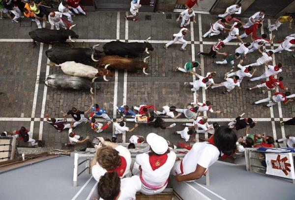 People on a balcony (bottom) watch runners on the street being chased by bulls from the Miura ranch during the eighth and last bullrun of Sanfermines in Pamplona, Navarra, northern Spain, July 14, 2017. EPA/JESUS DIGES