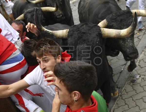 A bull from the Miura ranch charges at several runners during the eighth and last bullrun of Sanfermines in Pamplona, Navarra, northern Spain, July 14, 2017. EPA/DANIEL FERNANDEZ
