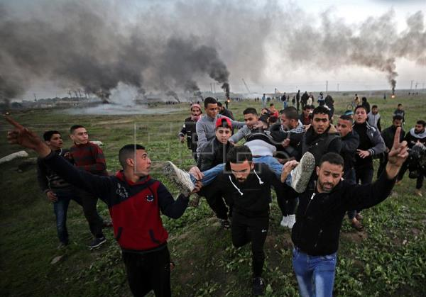 Palestinian protesters carry a wounded young man during clashes between Israeli troops and Palestinians near the border in eastern Gaza City, Jan. 12, 2018. EPA-EFE/MOHAMMED SABER