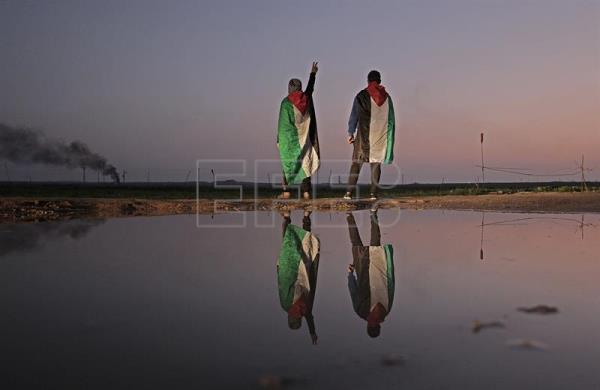 Two Palestinians protesters are reflected in a pond during clashes near the border between Israel and Gaza Strip, in the east Gaza City, Jan. 12, 2018. EPA-EFE/MOHAMMED SABER
