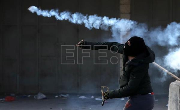 Palestinian protester throws back a tear gas grenade at Israeli troops during clashes at Huwwara checkpoint near the West Bank City of Nablus, Jan. 12, 2018. EPA-EFE/ALAA BADARNEH