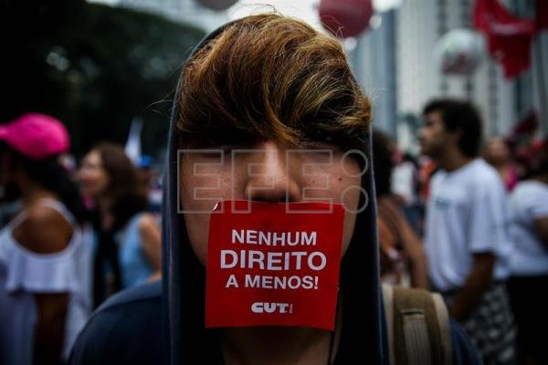 A demonstrator shows a small banner that reads: 'No right to less', during a demonstration in Sao Paulo, Brazil, Mar. 15, 2017. EFE/FERNANDO BIZERRA JR