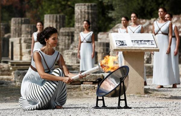 flame lighting olympics. greek actress katerina lechou, in the role of high priestess, lights torch flame lighting olympics