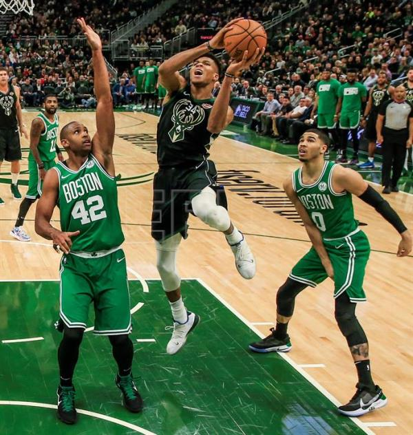 El jugador Giannis Antetokounmpo (c) de Milwaukee Bucks en acción ante Al Horford (i) y Jaylen Brown (d) de Boston Celtics, este jueves, durante un juego de la NBA entre Boston Celtics y Milwaukee Bucks en el Fiserv Forum en Milwaukee, Wisconsin (Estados Unidos). EFE