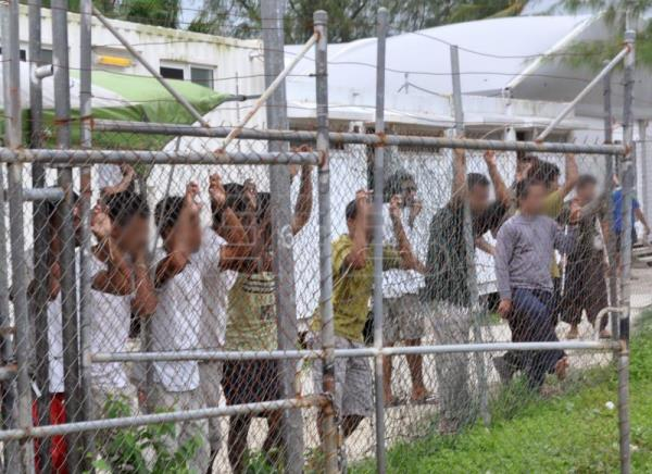 Asylum seekers stare from behind a fence at the Oscar compound in the Manus Island detention centre, Papua New Guinea, Mar. 21, 2014 (reissued Jun. 14, 2017). EPA-EFE FILE/EOIN BLACKWELL -- ATTENTION EDITORS: IMAGE PIXELATED AT SOURCE -- AUSTRALIA AND NEW ZEALAND OUT