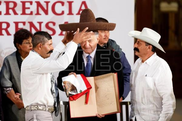 Mexican President Andres Manuel Lopez Obrador (c.) is given a Mexican sombrero by descendants of the revolutionary Emiliano Zapata on Jan. 11, 2019, at a press conference in Mexico City where he announced a new program of aid for disabled persons. EFE-EPA/Jose Mendez