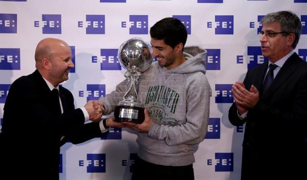 FC Barcelona's Uruguayan forward Luis Suarez (C) is presented with the EFE Award to the Best Latin American player in 2015 by the Spanish international news agency EFE's Sports Director, Luis Villarejo (L), in presence of FC Barcelona's Sports Deputy President Jordi Mestre during a ceremony held at the FC Barcelona sports city in Barcelona, northeastern Spain, 29 February 2016. EFE/Alberto Estevez