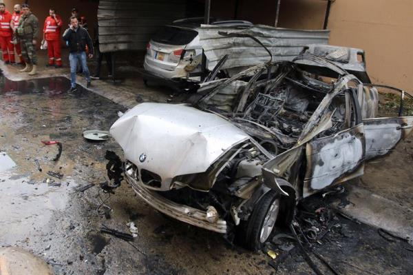 Firefighters and security officials stand near a damaged car at the site of car bombing that reportedly targeted a Hamas official, in Sidon, Lebanon, 14 January 2018. EFE