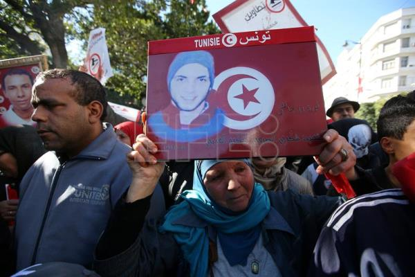 A woman holds a photo of a relative who was killed in the Tunisian uprising during a celebration to mark the seventh anniversary of the uprising that ousted president Zine El Abidine Ben Ali, at the Avenue Habib Bourguiba in Tunis, Tunisia, 14 January 2018. EFE