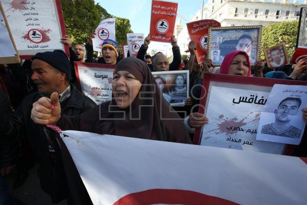 Relatives of those killed and wounded in the Tunisian uprising hold their photos and shout slogans during a celebration to mark the seventh anniversary of the uprising that ousted president Zine El Abidine Ben Ali, at the Avenue Habib Bourguiba in Tunis, Tunisia, 14 January 2018. EFE