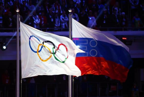 The Olympic flag (L) and the Russian flag (R) during the Closing Ceremony of the Sochi 2014 Olympic Games in the Fisht Olympic Stadium in Sochi, Russia, Feb. 23, 2014. EPA-EFE/HANNIBAL HANSCHKE