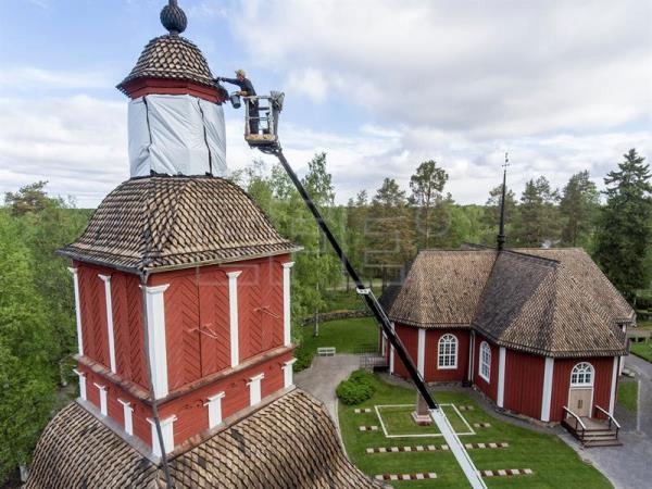 Tar Master Esko Puhto applies traditionally made pine tar on the roof of the Kiiminki church bell tower, in Kiiminki, Finland, June 21, 2017. EPA/MARKKU OJALA