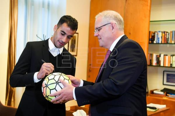Footballer and refugee Hakeem al-Araibi (L) signs a soccer ball for Australian Prime Minister Scott Morrison (R) during a meeting at Parliament House in Canberra, Australia, Feb. 14, 2019. EPA-EFE/LUKAS COCH AUSTRALIA AND NEW ZEALAND OUT