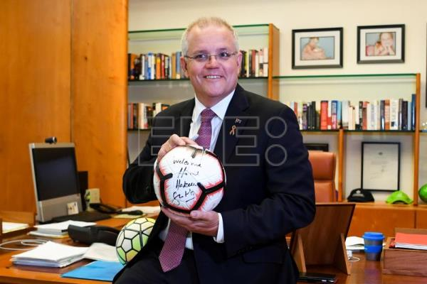 Australian Prime Minister Scott Morrison poses for photos with a ball he wrote on before meeting footballer and refugee Hakeem Al-Araibi at Parliament House at Parliament House in Canberra, Australia, Feb. 14, 2019. EPA-EFE/LUKAS COCH AUSTRALIA AND NEW ZEALAND OUT