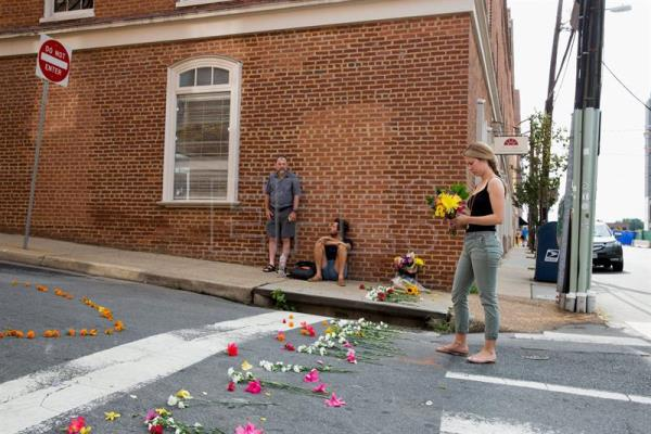 People gather and place flowers at the corner of Fourth Street and Water Street, where a car plughed into a crowd of people at a rally, Charlottesville, Virginia, USA, 13 August 2017. EFE